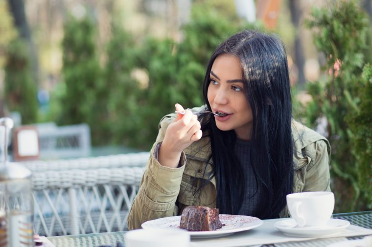 Close up portrait of a young woman eating dessert chocolate ice cream licking spoon outdoors in summer terrace coffee shop. Side view