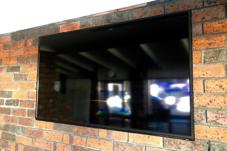 A flat-screen television mounted against a red brick wall.