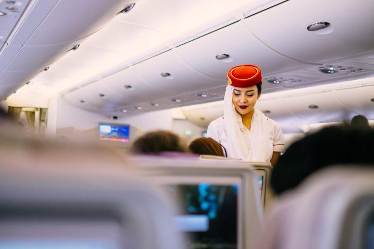 Dubai, UAE - JUNE 09, 2017: Emirates Airbus A380 economic class seats. In-flight entertainment system. Emirates cabin crew member, flight attendant. Airline food, dining, meals.