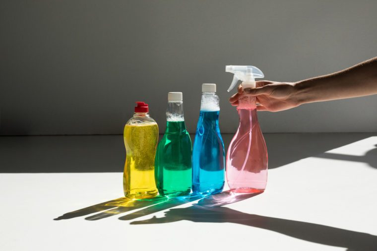 partial view of hand holding spray bottle and various cleaning fluids on white