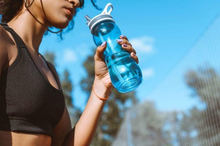Cropped shot of woman in sports bra drinking from blue water bottle