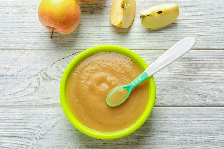 Plastic bowl with baby food on wooden background