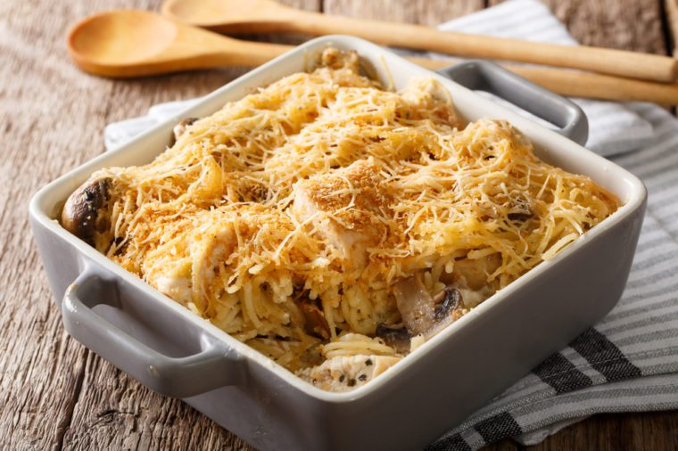 American tetrazzini with spaghetti, mushrooms, cheese, chicken close-up in a plate for baking on a table. horizontal