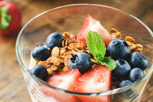 Berries with granola and mint leaf in glass. Concept of healthy eating, gluten-free diet, healthy lifestyle. Closeup view. Banner. Horizontal composition