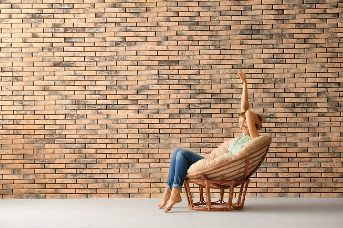 Young woman resting in lounge chair near brick wall