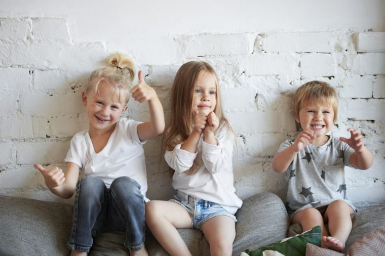 Candid shot of three siblings posing in living room, sitting on top of sofa at white brick wall: blond boy showing thumbs up gesture, girl in the middle pumping fists and their little sister grimacing