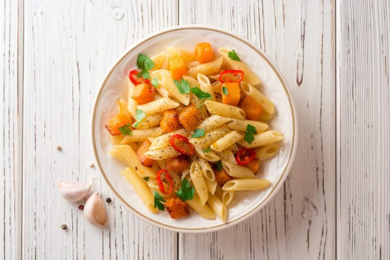 Penne pasta with pumpkin, chilli and parsley in plate on white wooden background. Top view. Copy space.