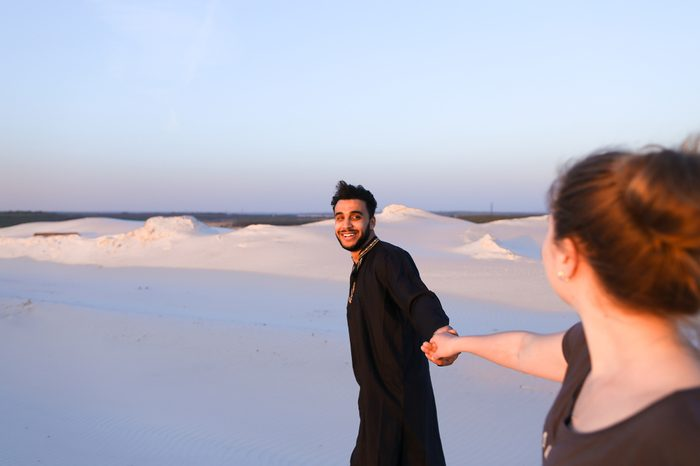 Handsome male Arab holding woman's hand, chatting and smiling looking at her. Lovers walk through expanses of sandy desert at sunset under open blue sky on summer evening. dark man with short dark
