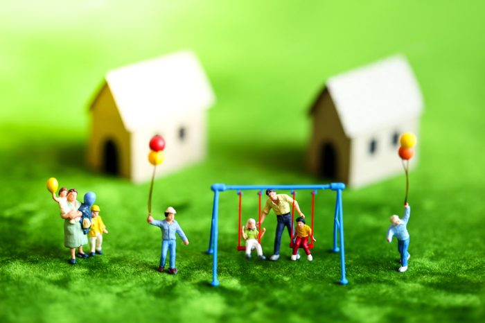 Miniature people with happy family holding balloons in front of wooden house on green background as property or mortgage concept.