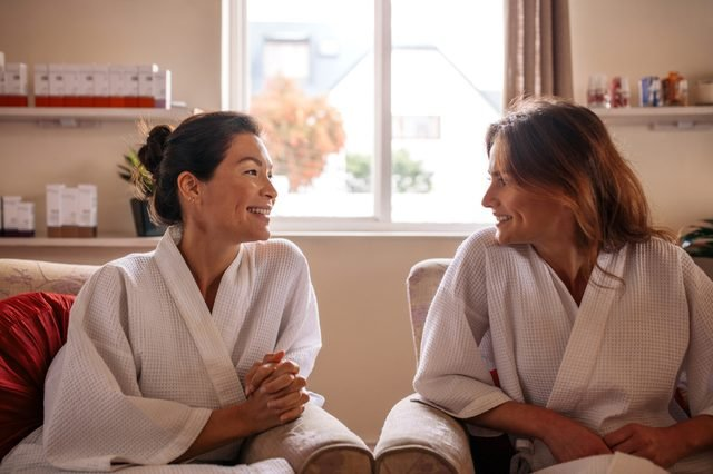 Woman friends in wellness spa waiting room, talking and smiling. Females in bathrobe sitting in health spa reception area and waiting for their spa treatment.
