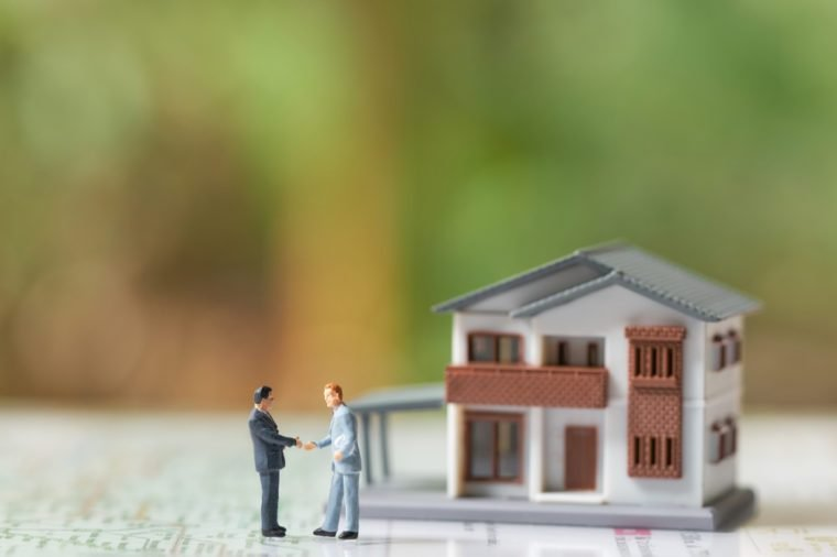 Miniature 2 people businessmen Shake hands with A model house model .as background business concept and real estate concept with copy space.