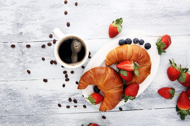 coffee and croissant with coffee beans. breakfast energy concept