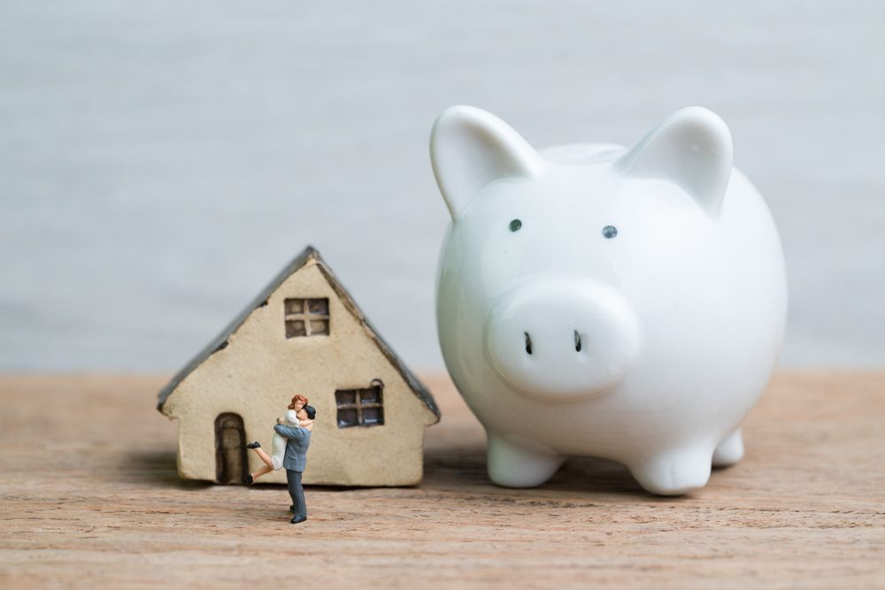 Miniature people, lovely couple happiness husband and wife with house and huge piggy bank using as success saving marriage life.
