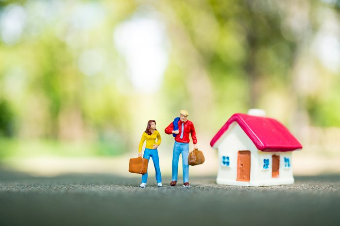 Miniature people, man and woman standing with mini house on green nature background using as business, financial and family concept