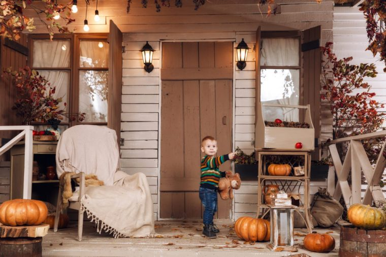 Cute little baby boy dressed in a sweater, jeans, blue boots playing near house with plush toy teddy bear in autumn time. Courtyard, lit by flashlights, with dry fall yellow leaves, orange pumpkins