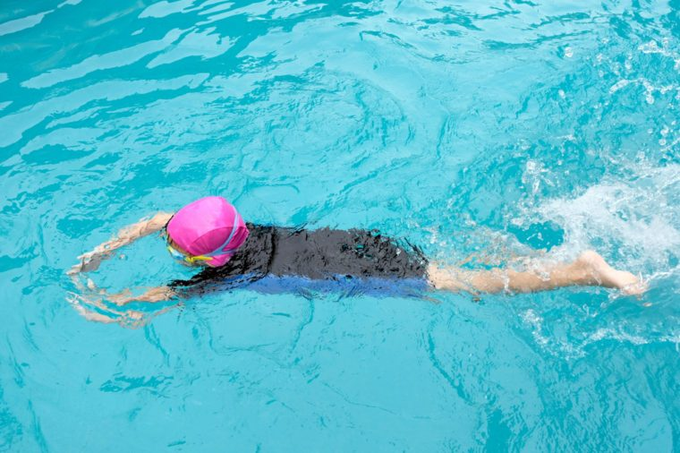 The girl is swimming in a blue pool.