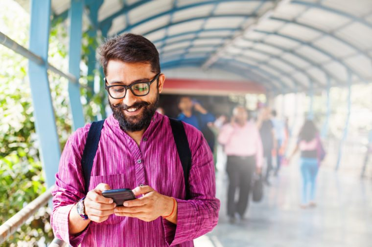 Bearded indian man on metro station using app in his smartphone