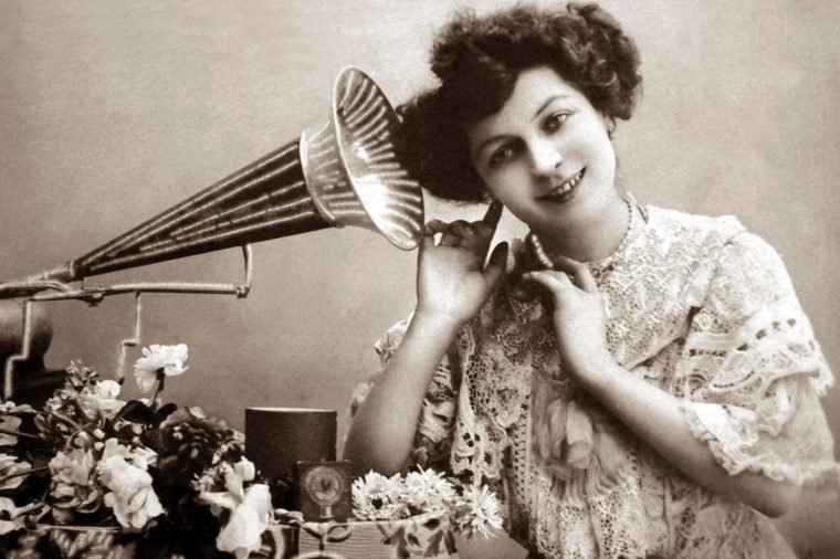 Woman listening to music with gramophone