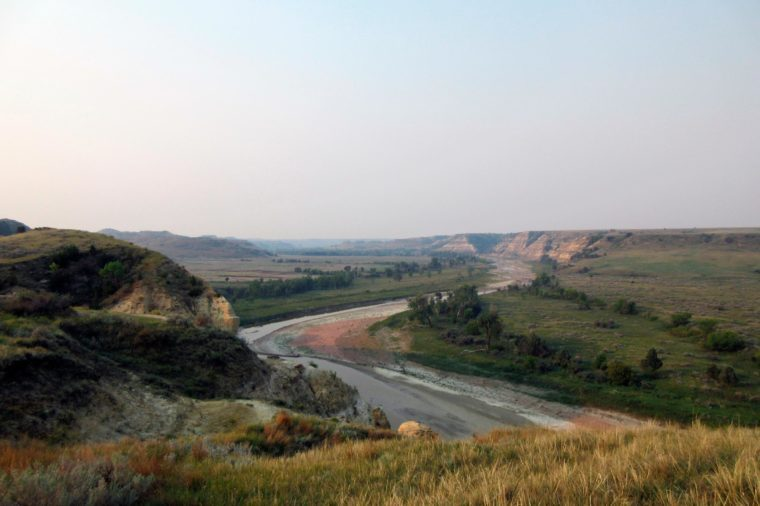 "This photo shows a curving river at Theodore Roosevelt National Park in Medora, N.D., marking the landscape in colorful patterns as it interacts with soil and stone. Teddy Roosevelt spent time in the area to grieve after his wife and mother died the same day, and his experiences there turned the future president into one of America's greatest conservationists. He described the area as ""a land of vast silent spaces _ a place of grim beauty"