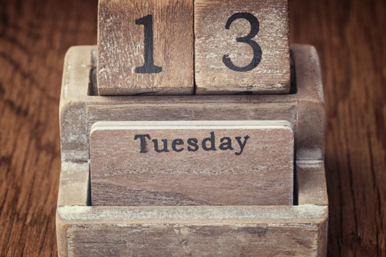Grunge calendar showing Tuesday the thirteenth on wood background