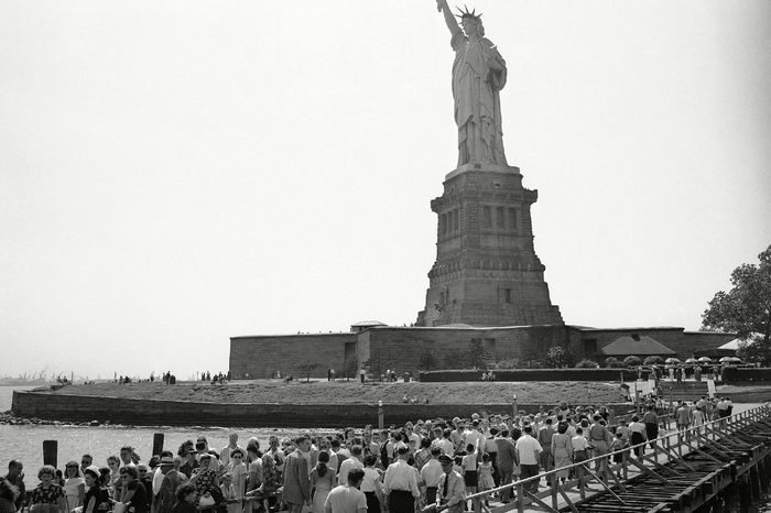 Visitors leaving the pier pass those moving toward the base of the Statue of Liberty on Bedloe's Island in New York's harbor on . Summer week-ends are especially busy, as tourists crowd the excursion boats which travel to the island from the foot of Manhattan Island