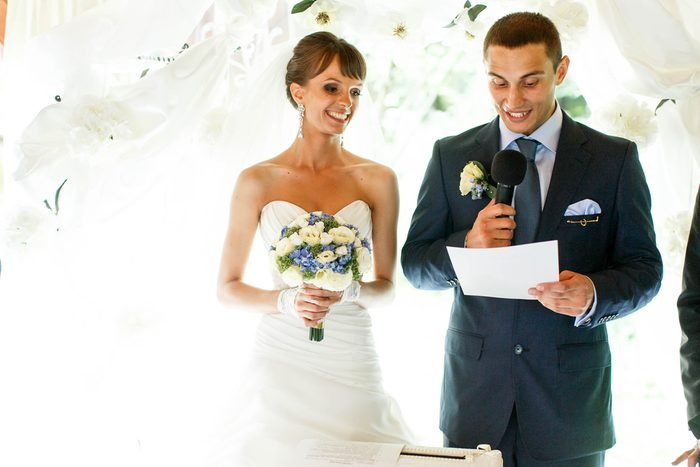 smiling groom and bride on the background white curtains