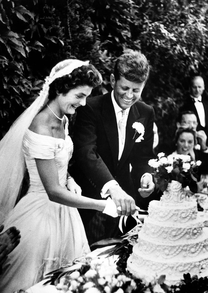 John F. Kennedy and Jacqueline Bouvier cut the cake
