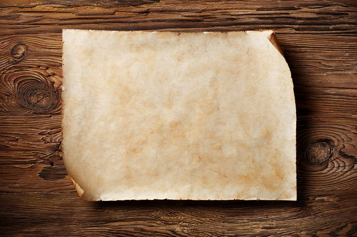 old blank parchment on aged wood background,horizontal