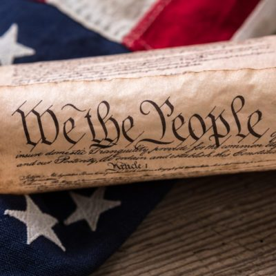 United States Constitution, rolled in a scroll on a vintage American flag and rustic wooden board