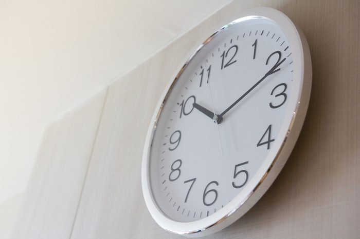 white metal clock on wooden wall with warm light in late morning