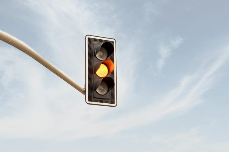 Yellow traffic light on a horizontal white metal beam, isolated on sky background