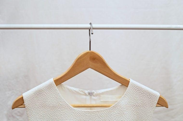 Light ladies sleeveless o-neck blouse on wooden hangers on light background