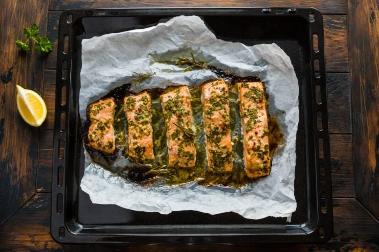 Salmon roasted in an oven with a butter, parsley and garlic. Cooked fish on a baking sheet on the wooden background, top view.