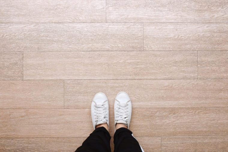 Selfie Of Feet In Fashion Sneakers On Wooden Floor Background Top View With Copy E