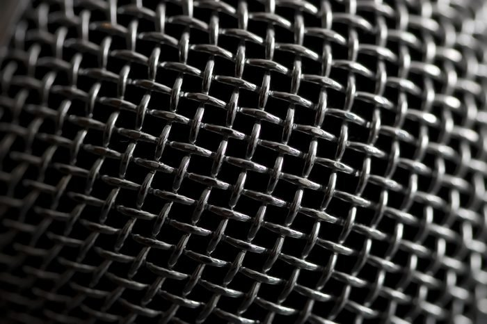 Steel grille background. Close-up shot of microphone.