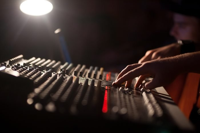 Sound technician and lights technicians control the music show in night club.Professional audio,light mixer controller panel.Pro equipment for concerts.Stage lighting control