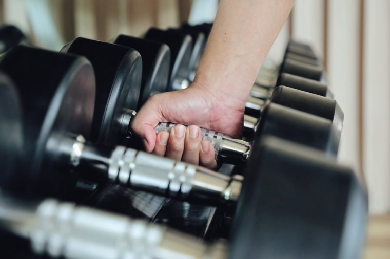 Hand holding dumbbell in the gym bodybuilding, Close up. Muscular arm in the fitness center. Training, sports,The concept of a healthy lifestyle and fitness. article about fitness and sports.