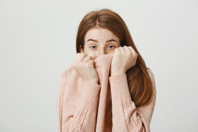 Studio portrait of cute redhead caucasian student covering half face with pullover, looking out of collar and standing over gray background. Friends' cooking smells awful and girl tries not to breath