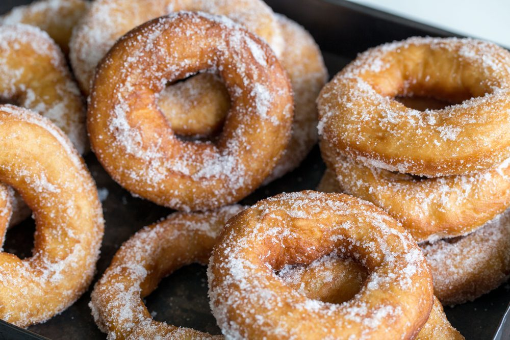 Homemade donuts with sugar and sugar powder in old metal background.