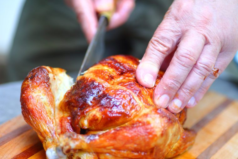 A man steadies a chicken with one hand as he cuts with the other