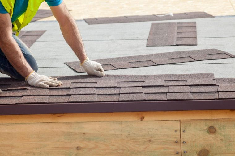 Roofer builder worker installing roof shingles