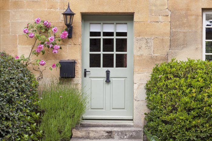 Light green wooden doors in an old traditional English lime stone cottage surrounded by climbing pink roses, lavender, on summer day