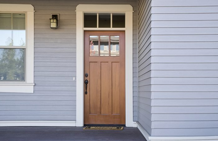 Closed wooden front door of a house during daytime