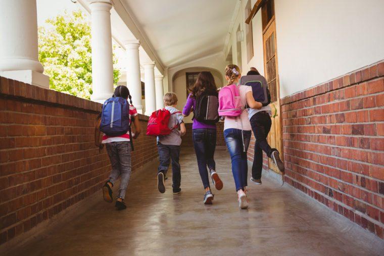 Full length rear view of school kids running in school corridor
