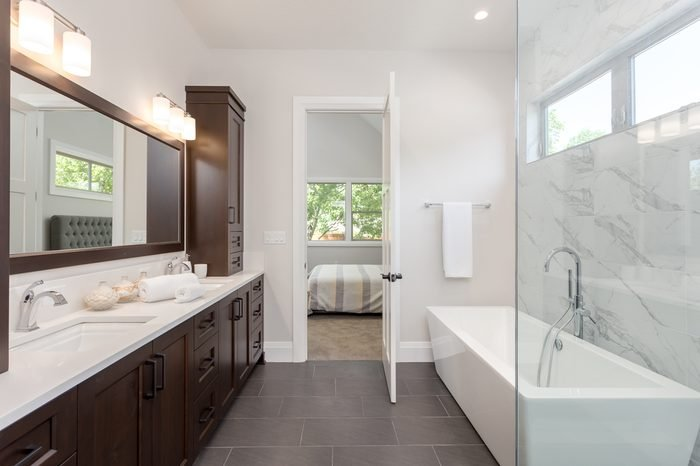 Master bathroom in new luxury home. Tile stretches from floor to ceiling behind bathtub, and partial glass wall hints at luxurious shower. Dark wood cabinetry surrounds double vanity; two sinks.