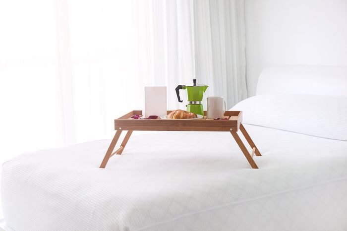Breakfast wooden tray with coffee percolator, white blank card and croissant on bed. Light from window inside the room