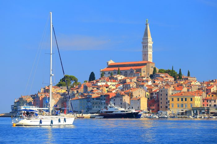 Tall sail boat enters the harbor of old Venetian town of Rovinj, Croatia