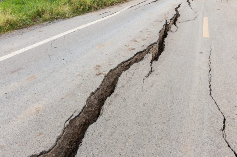 Cracked and broken asphalt road from earthquake.