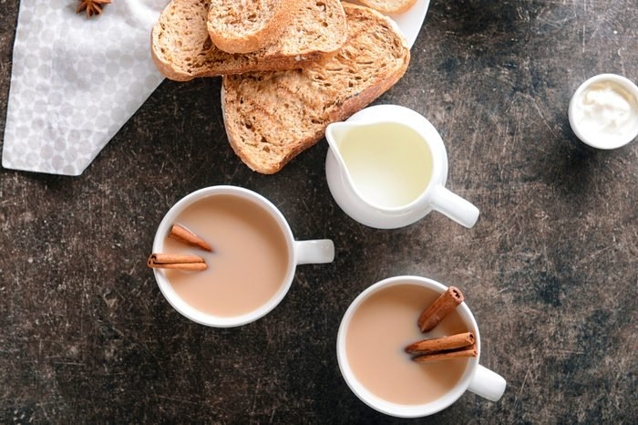 Cup of aromatic tea with cinnamon, milk and fresh bread on table