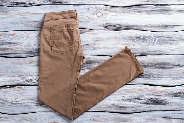 Woman's brown casual pants. Brown trousers on wooden background. Pants made of natural material. New item at low price.